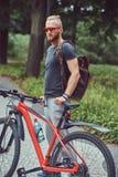 与在运动服和太阳镜步行和胡子的一个英俊的红头发人男性穿戴的一个时髦的理发在有a的公园 库存图片
