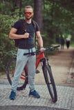 与在运动服和太阳镜步行和胡子的一个英俊的红头发人男性穿戴的一个时髦的理发在有a的公园 免版税库存图片
