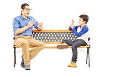年轻与在长凳安装的他的更老的表兄弟的男孩纸牌 库存照片