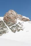与在雪报道的它的倾斜的山上面 免版税库存图片