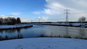 与在雪报道的运河交叉点的荷兰冬天风景 免版税图库摄影