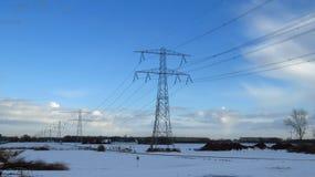 与在雪盖的传输塔的冬天风景 库存照片