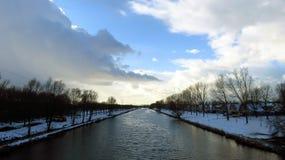 与在雪盖的运河银行的冬天风景 免版税库存照片