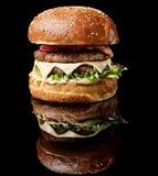 与在黑背景与反射隔绝的新鲜蔬菜的大肥胖汉堡 库存图片