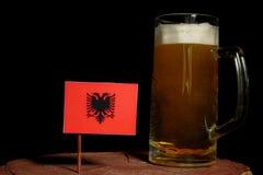 与在黑色隔绝的啤酒杯的阿尔巴尼亚旗子 库存照片