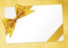 与在黄色隔绝的金黄丝带弓的礼品券 库存照片