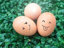 与在绿草上把放的微笑图画的三个鸡蛋 免版税库存照片
