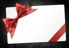 与在黑backgroun隔绝的红色丝带弓的礼品券 免版税库存图片