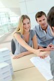 与地产商的年轻夫妇握手 库存照片