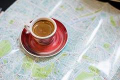 与地图的早晨咖啡在微型咖啡馆的travelmorning的咖啡的与旅行指南的地图 免版税库存照片