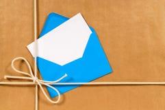与地址标码或礼品券和蓝色信封的包装纸背景 库存照片