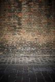 与地板的老砖墙背景 库存图片