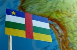 与地球地图的中非共和国旗子作为背景 免版税库存图片