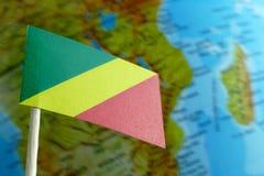 与地球地图的刚果共和国旗子作为背景 免版税库存照片