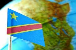 与地球地图的刚果民主共和国旗子作为背景 免版税库存图片