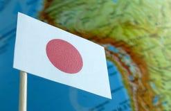 与地球地图的日本旗子作为背景 库存照片