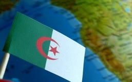 与地球地图的阿尔及利亚的旗子作为背景 图库摄影