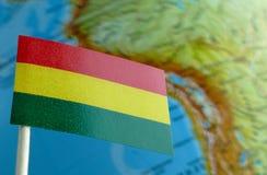 与地球地图的玻利维亚的旗子作为背景 库存图片