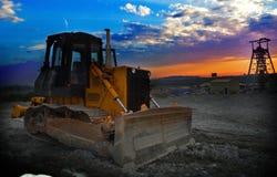 与地球搬家工人机器的矿井日出 免版税库存照片