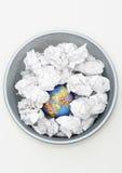 与地球的废物箱在被弄皱的纸视图中从上面 库存照片