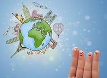与地球的著名地标的快乐的手指面带笑容 免版税图库摄影