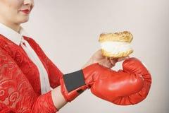 与坏食物,把装箱的奶油饼蛋糕战斗的妇女 免版税库存图片