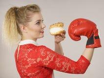 与坏食物,把装箱的奶油饼蛋糕战斗的妇女 库存图片