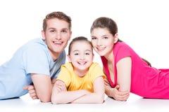 与坐在五颜六色的衬衣的孩子的微笑的家庭 图库摄影