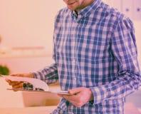 与坐在办公室的红色文件夹的微笑的商人 库存照片