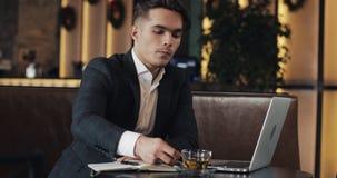 与坐在咖啡馆的smartwatch的年轻成功的商人 自由职业者景色消息,激活应用 股票视频