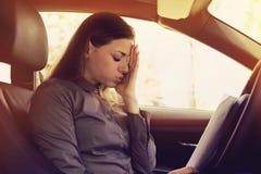 与坐在她的汽车里面的纸的被注重的妇女司机 免版税库存图片