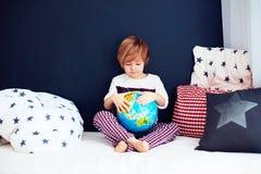 与坐在床上和探索新视野号的地球的逗人喜爱的孩子 免版税库存照片