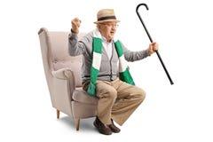 与坐在扶手椅子的藤茎和围巾的快乐的年长体育迷 免版税图库摄影