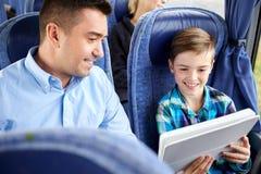 与坐在旅行公共汽车上的片剂个人计算机的愉快的家庭 免版税库存图片