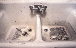 与坐在杂乱脏家伙的干画笔的肮脏的老白色瓷工作水槽 库存照片