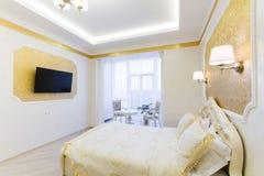 与坐垫的豪华床在皇家卧室内部 免版税库存图片