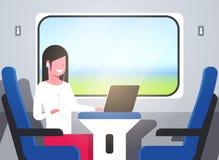 与坐蓝色扶手椅子铁路旅行的概念的耳机旅游女孩的妇女火车乘客听的音频书 皇族释放例证