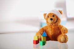 与块形状的被包扎的玩具熊在表上 免版税库存图片