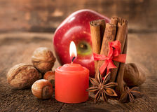 与坚果、八角、桂香和一个蜡烛的苹果计算机 库存照片
