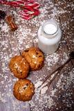 与坚果、葡萄干、棒棒糖和瓶的自创麦甜饼在黑暗的木背景,特写镜头的牛奶,有选择性 图库摄影