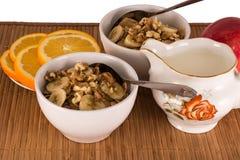 与坚果、香蕉、桔子和苹果的燕麦粥 免版税库存图片