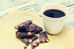 与坚果和一个杯子的黑暗的巧克力在被弄皱的纸的无奶咖啡 库存图片