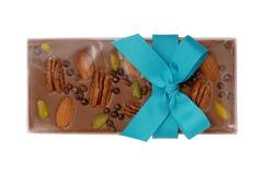 与坚果和一把蓝色装饰弓的巧克力块 免版税库存图片