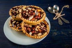 与坚果和焦糖的微型馅饼 免版税库存图片