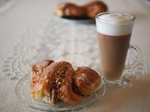 与坚果和罂粟种子的转动新月形面包与大咖啡拿铁 图库摄影