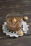 与坚果和饼干的巧克力沫丝淋在一个玻璃烧杯 库存图片