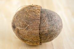 与坚果壳的充分的椰子在木bambo桌上 免版税库存照片