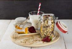 与坚果的格兰诺拉麦片在玻璃瓶子,草莓,杯牛奶 免版税库存图片