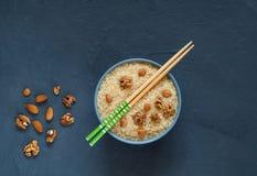 与坚果的白米在有在黑暗的背景隔绝的筷子的一个蓝色碗 亚洲食物,拷贝空间,顶视图, minimalismn 库存照片