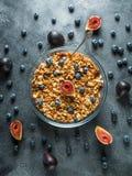 与坚果的自创鲜美muesli在玻璃碗、莓果和无花果结果实 健康素食早餐 免版税库存照片